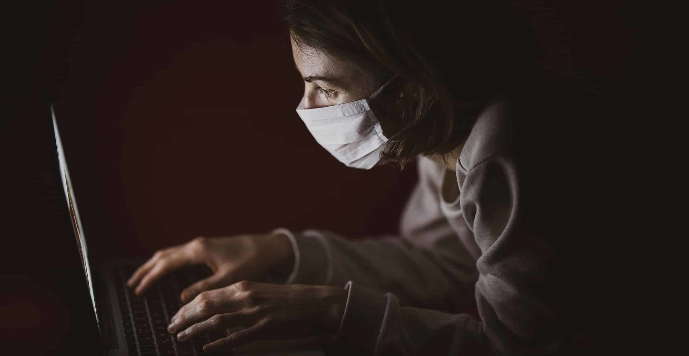 A woman wearing a face mask types on a laptop computer