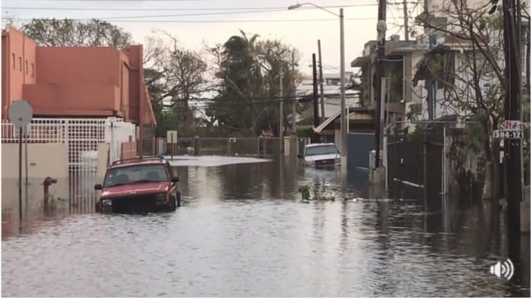 Two cars on a flooded street.
