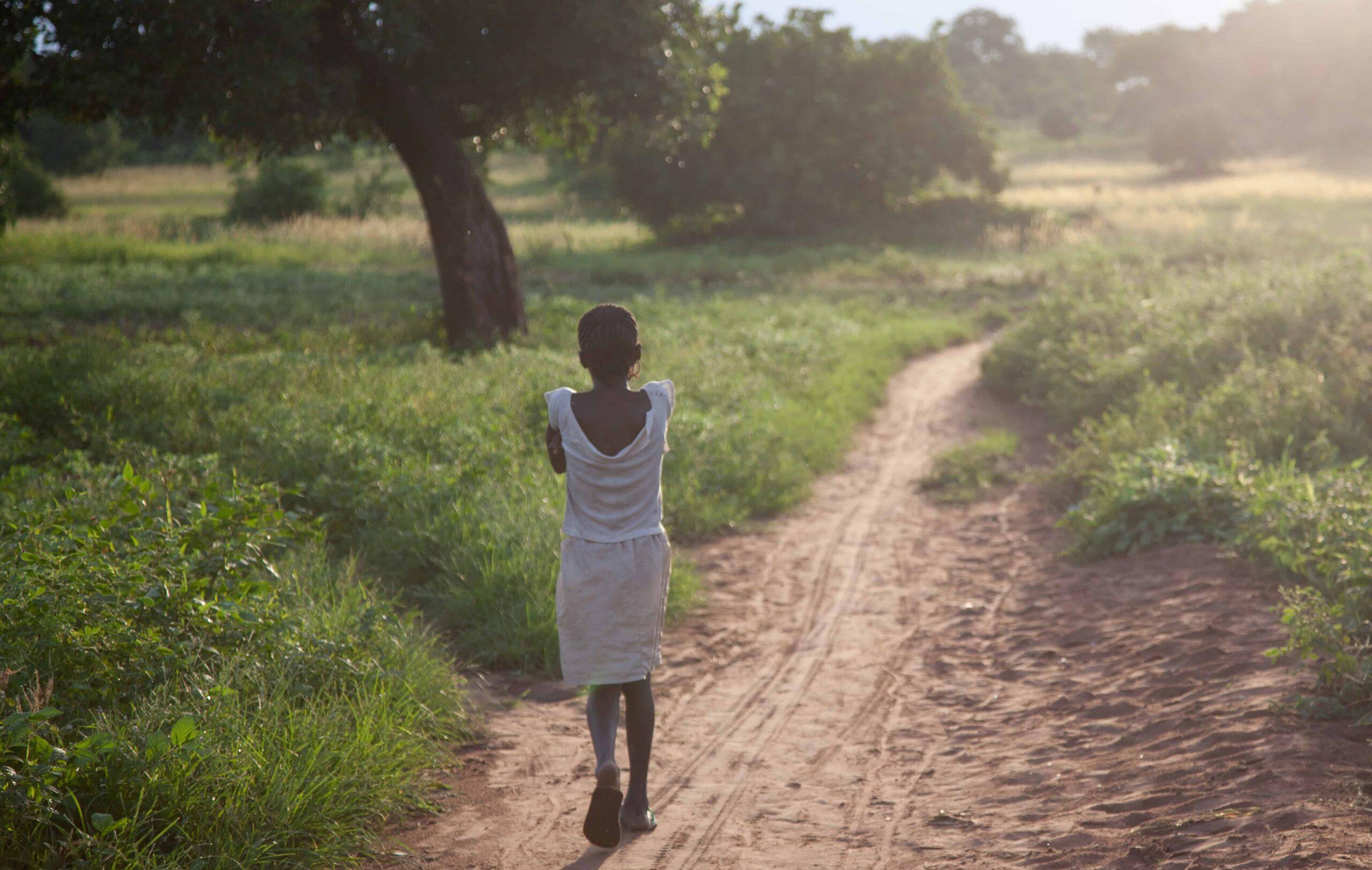 A girl in a white dress walks on a dirt path through a field
