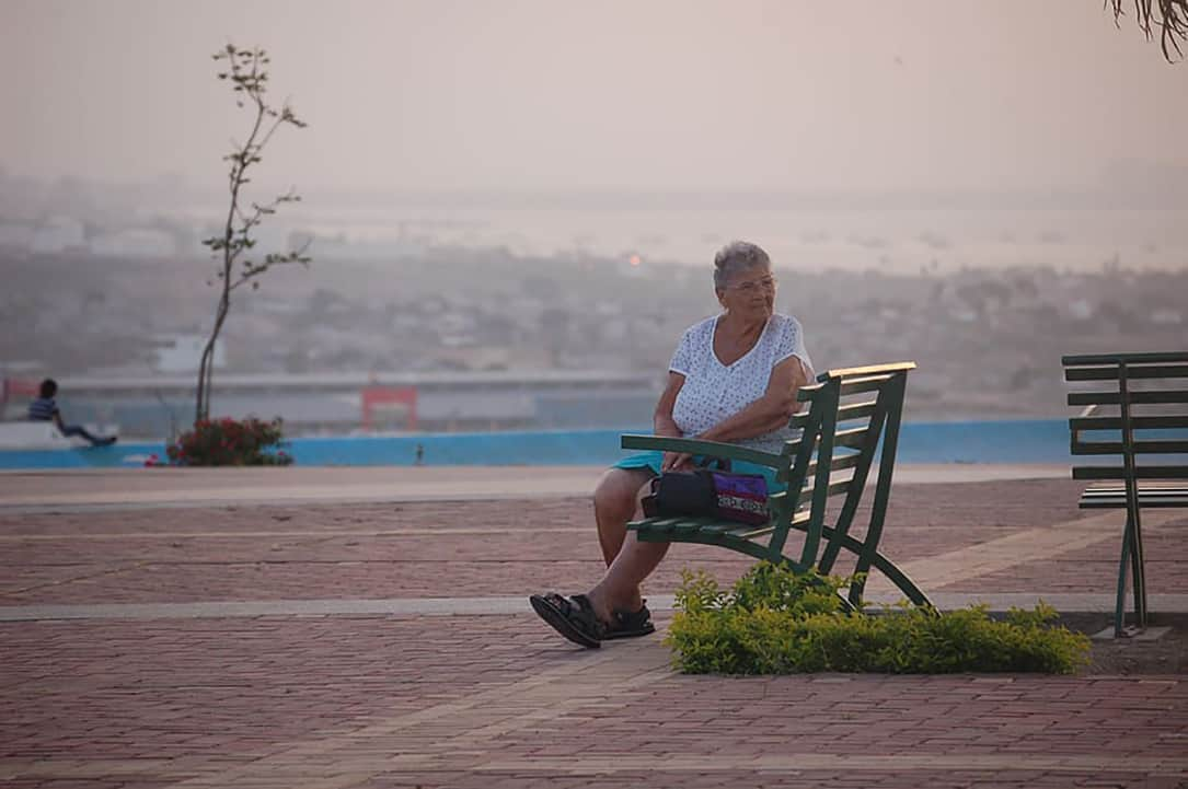 A woman sits by herself on a bench.