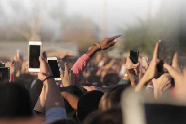 hands up in air with phones