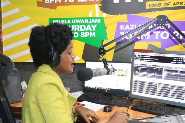 Woman at a mic in a radio station.