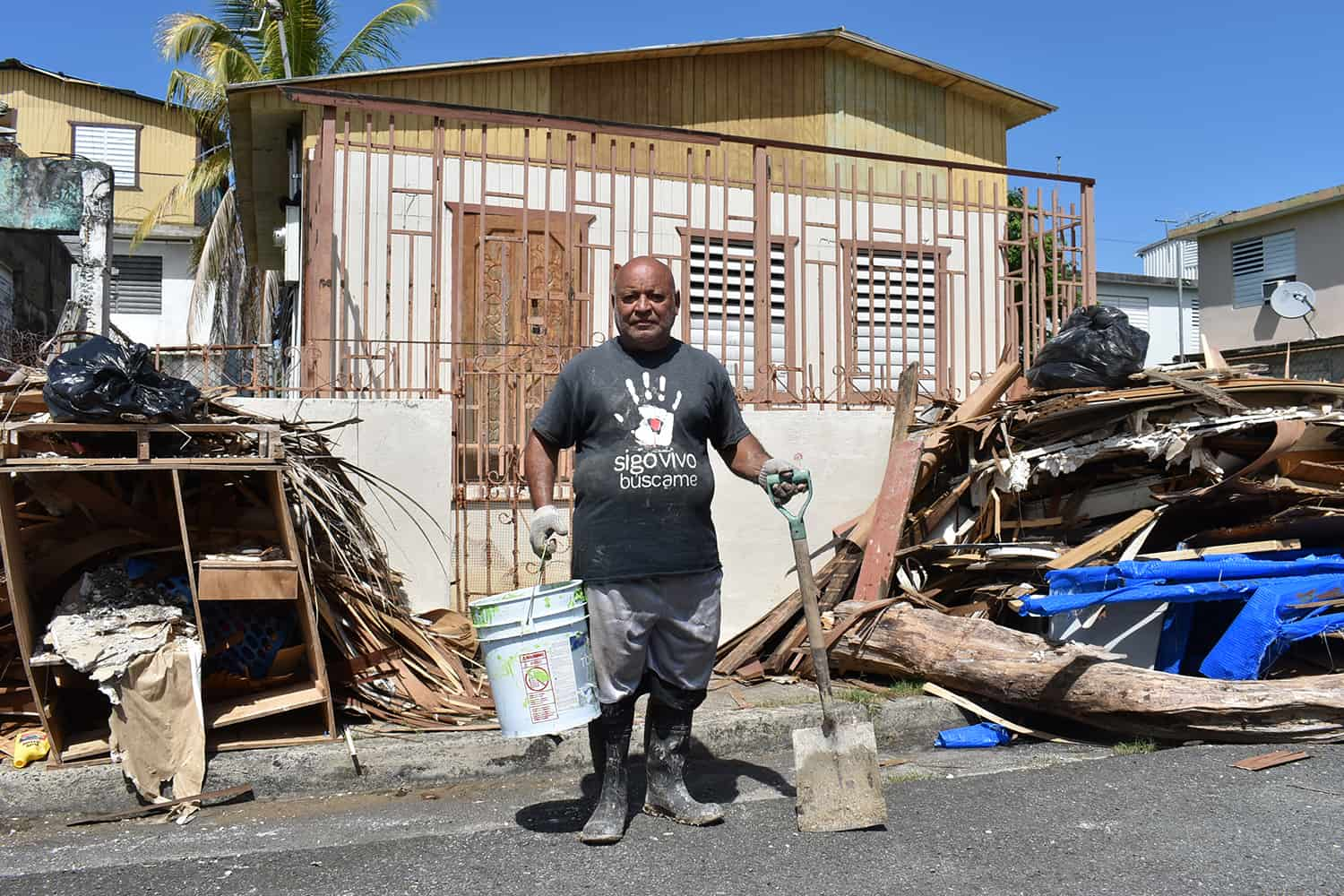A man stands in the street in front of a house, holding a bucket and shovel