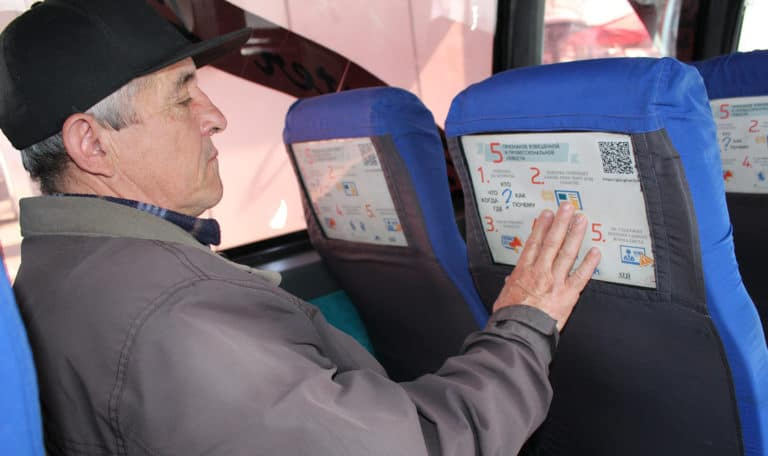 A man sitting on a bus reads the poster mounted on the seat in front of him.