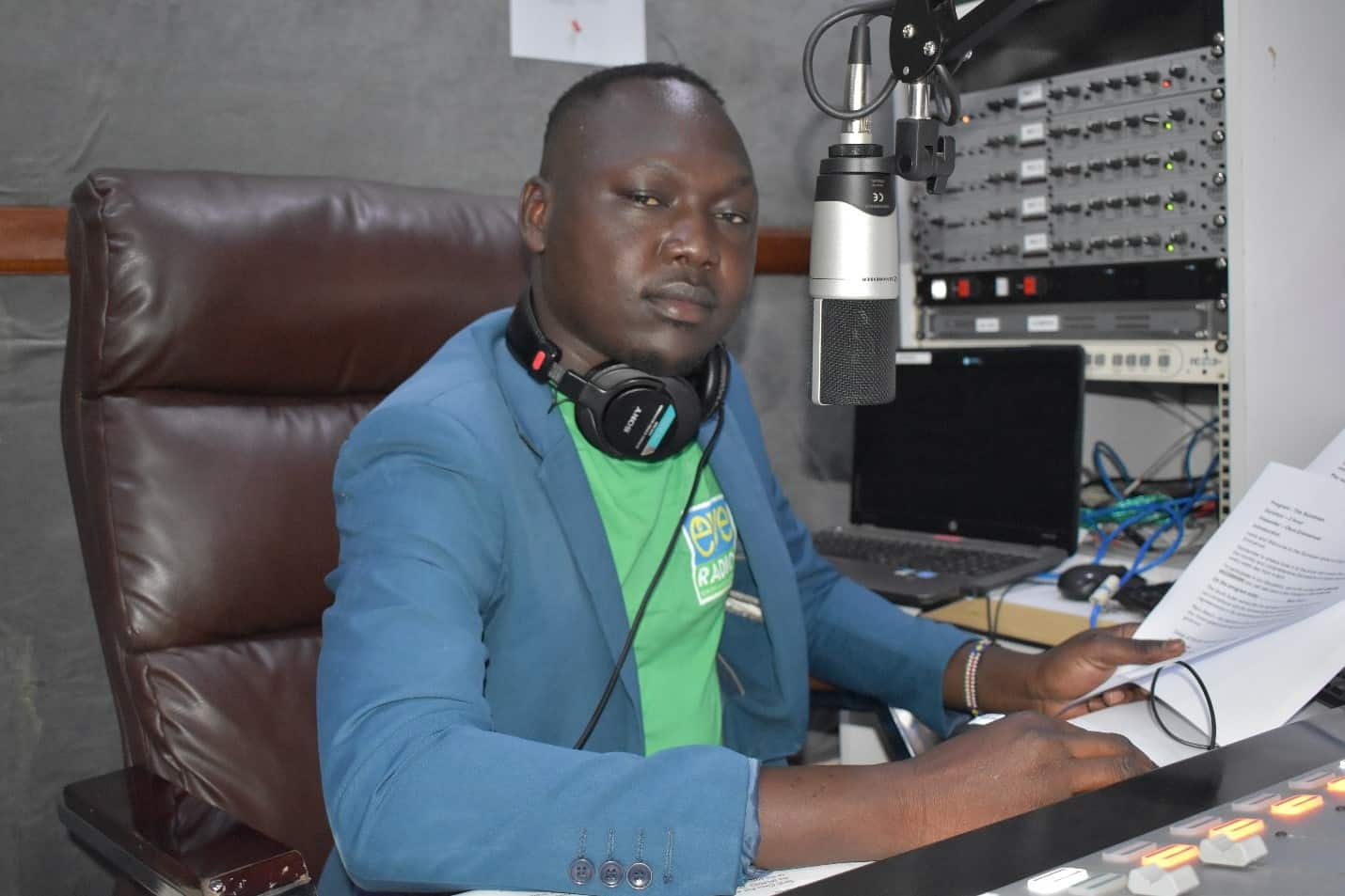 A man sits in front of a mic in a radio studio