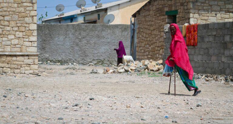 A woman using crutches crosses a dirt courtyard.