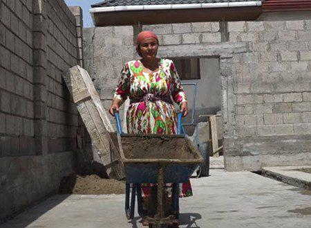 A woman pushes a wheelbarrow