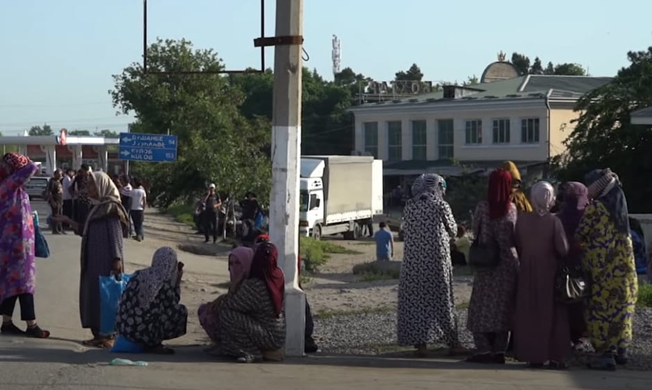 A group of women stand on a street corner
