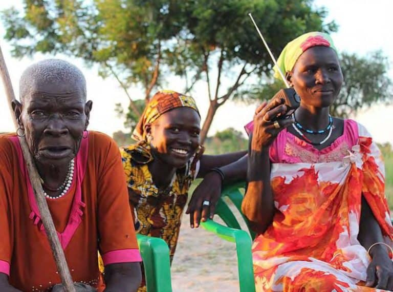 An older woman and two younger women sit outside listening to a portable radio.