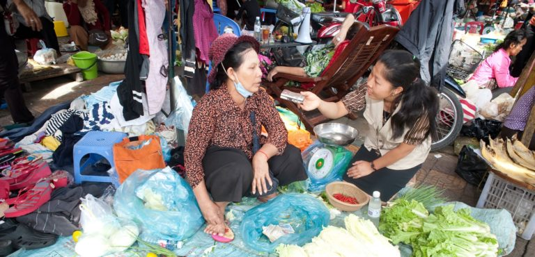 A journalist interviews a woman selling vegetables in a market.