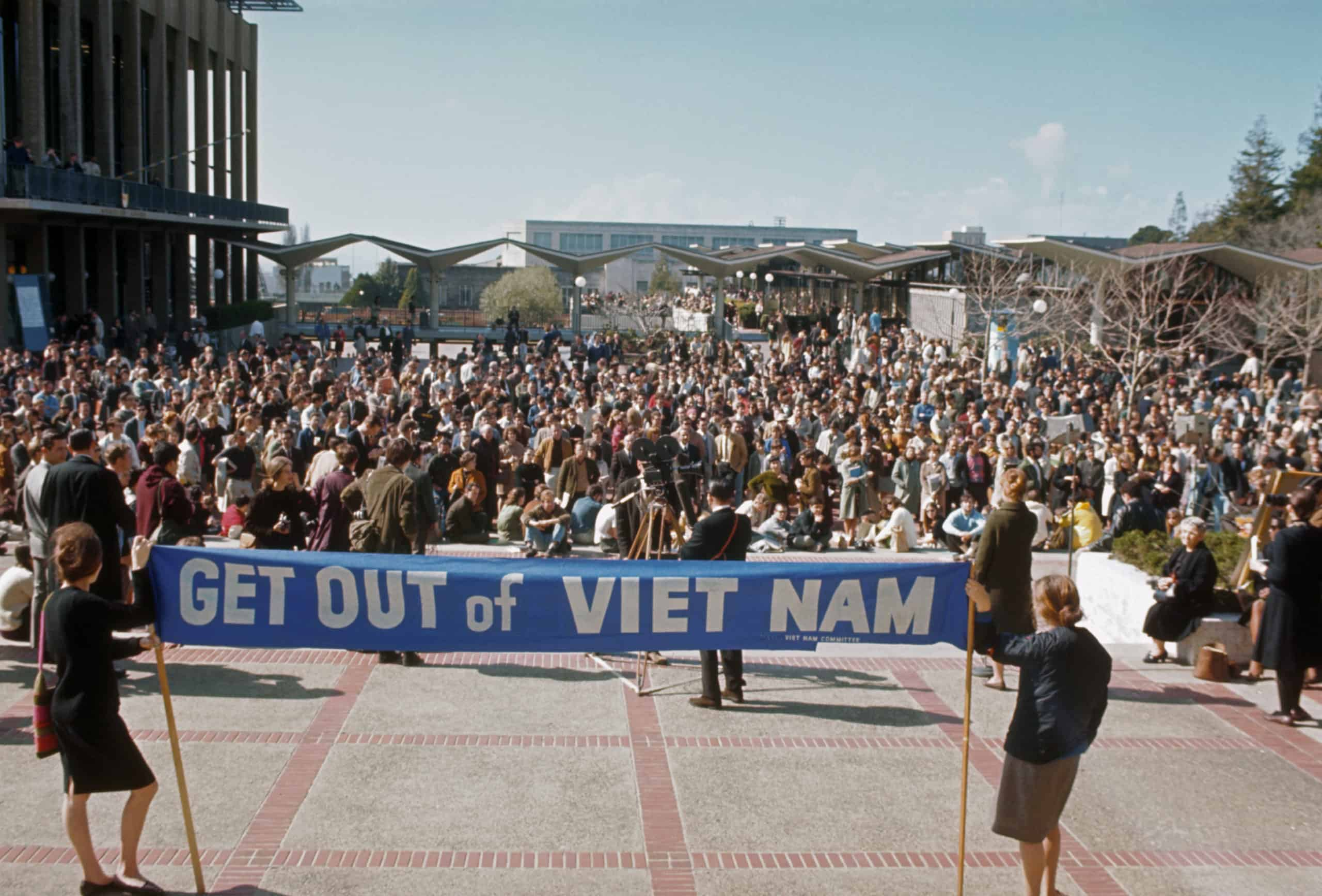 """Two people hold a banner saying """"Get out of Vietnam"""" at a protest."""