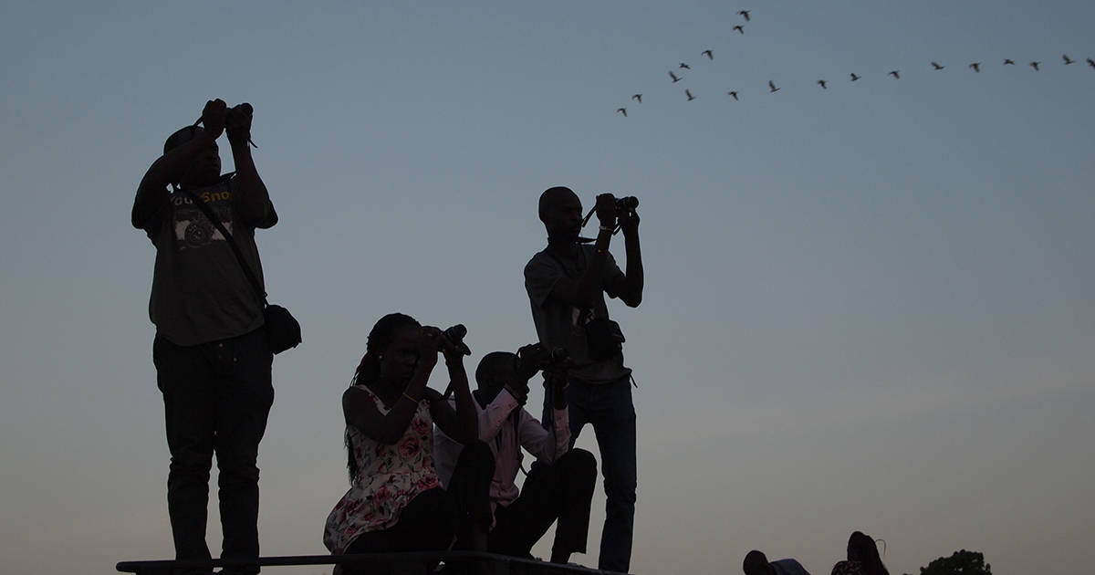 A group of people with cameras stand on a hill