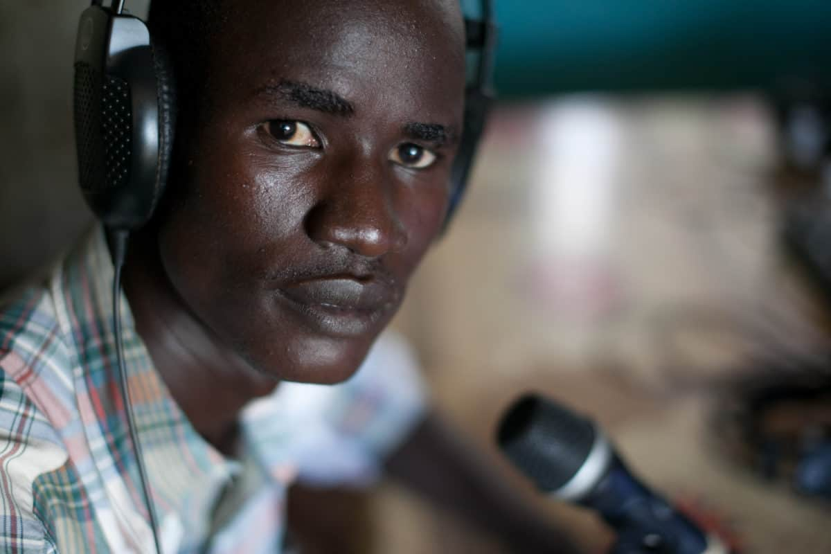 A man wears head phones and sits in front of a mic
