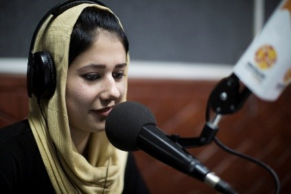 A woman wearing a head scarf sits in front of a microphone