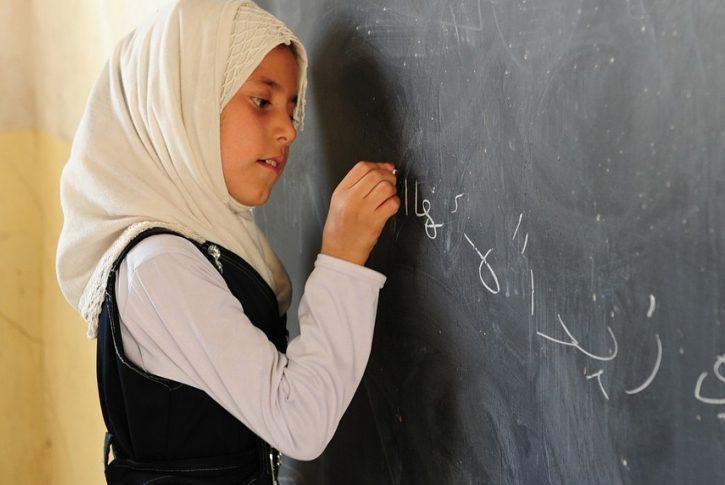 A young girl wearing a headscarf writes in chalk on a blackboard