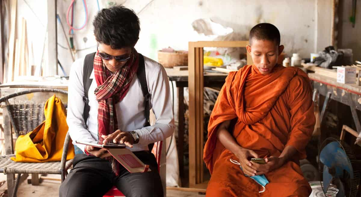 A man in a white shirt, dark pants, sunglasses, and wearing a backpack sits working on a tablet. Another man sits next to him, wearing an orange robe and looking at a smart phone.