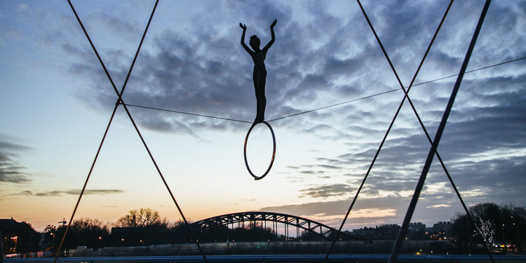 A person balances on top of a hoop