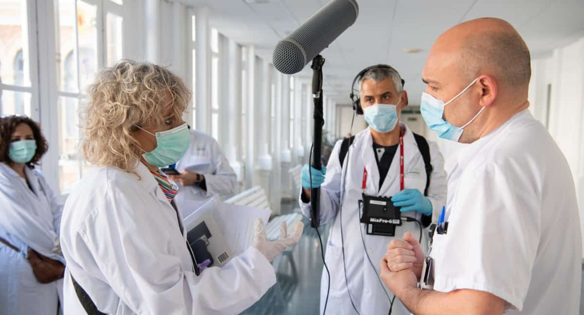 A woman wearing a face mask talks to a man wearing a face mask, while another man records them on a mic
