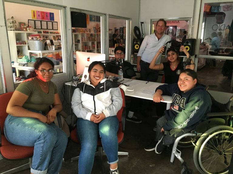 A group of young women, one of them using a wheelchair, sit in a room with audio equipment; an older man stands behind them.