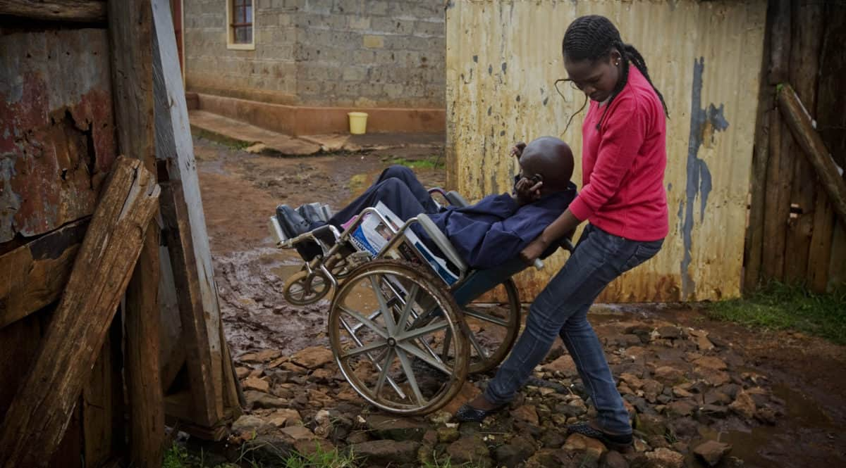 A woman pushes a man in a wheelchair, tipping the chair back to get over rough ground.