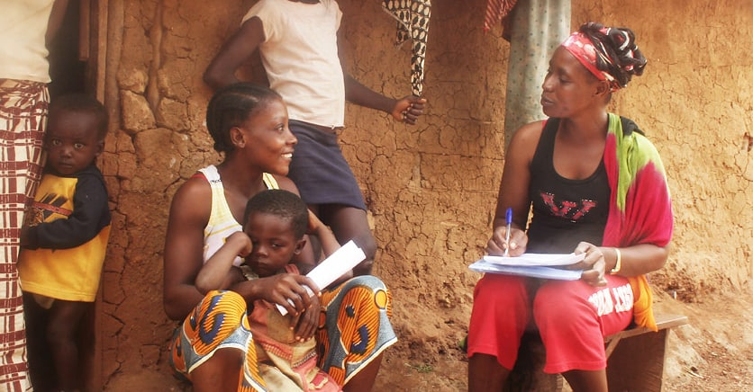 A woman sits on a bench next to a mud brick wall, writing on a pad of paper; a woman sits next to her holding a child on her lap. Two other children stand nearby.