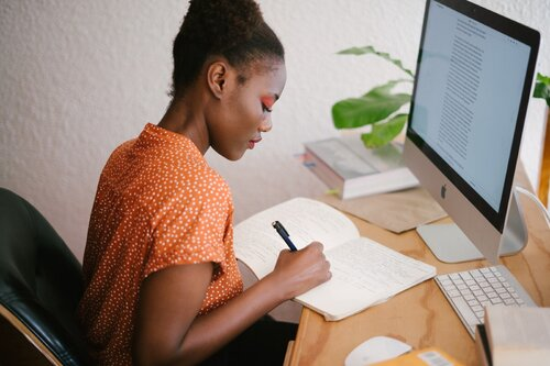 A woman writes in a notebook while sitting in front of a monitor.