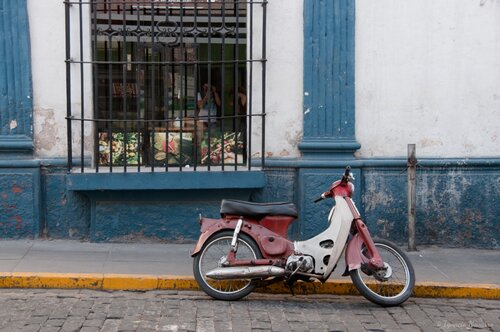 A motorbike is parked by the curb on a cobblestone street.