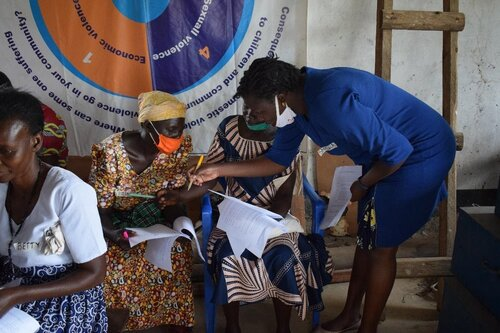 A woman points to something on a woman's arm, who is seated.