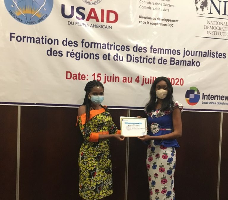 Two women wearing face masks stand on a stage, holding a certificate.