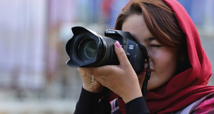 A woman wearing a scarf looks through the sight of a camera