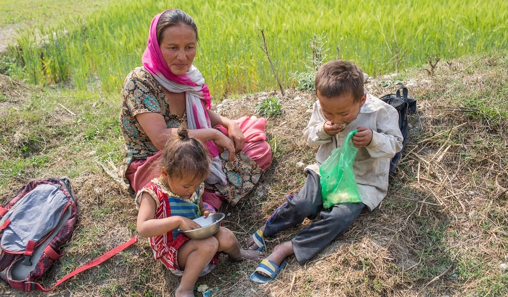 A woman sits outside on the grass with two children who are eating