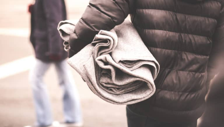 A person wearing a down jacket holds a blanket under their arm.