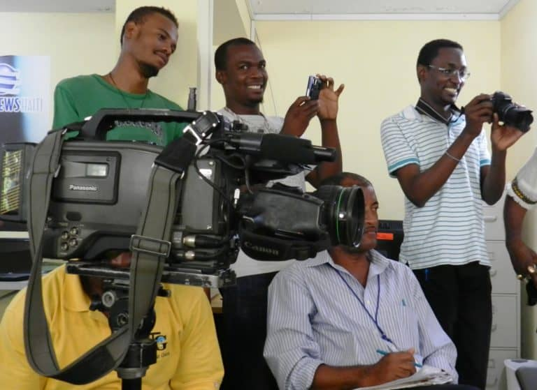 Five men stand in a room; some using smart phones; one has a video camera.