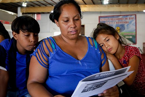A woman reads a newspaper while two children look on