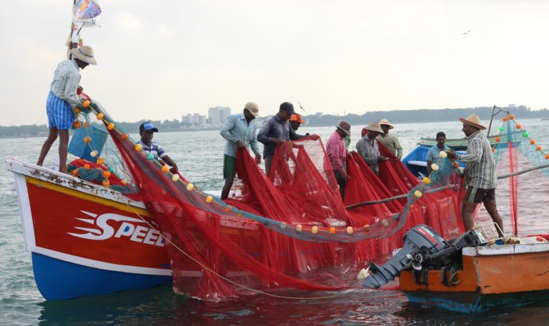 Men pull nets on to a fishing boat