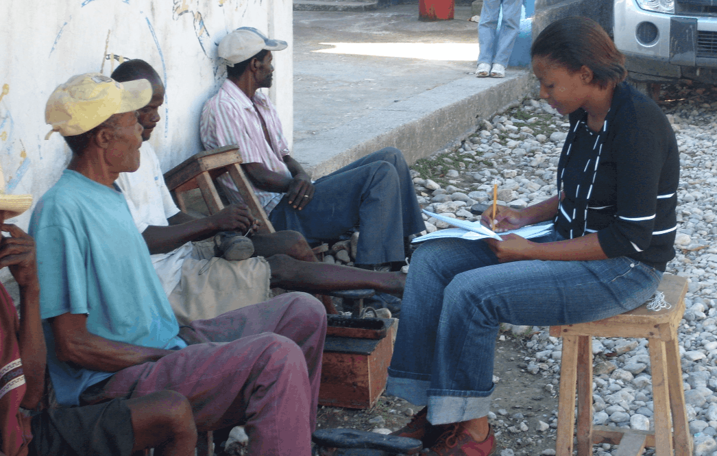 A woman sits on a stool outside a building writing on a paper on her lap; 3 men sit across from her