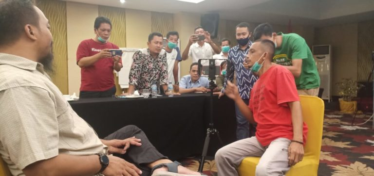 A group of men gather around a table looking at a smart phone camera at another man who is seated.