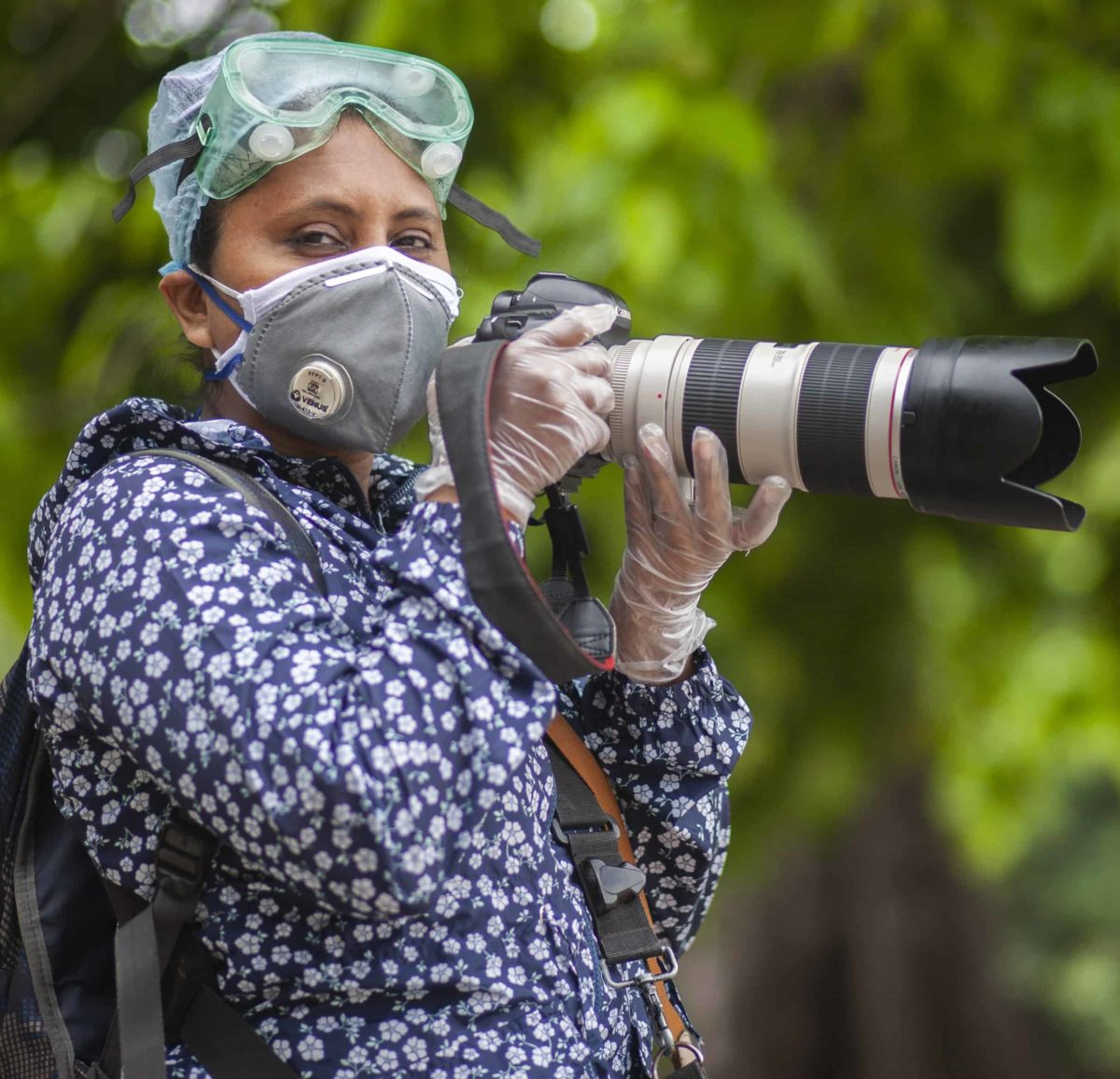 A woman wearing PPE holds a camera.