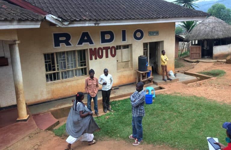"""Four people stand in front of a small concrete building with a sign """"Radio Moto"""""""