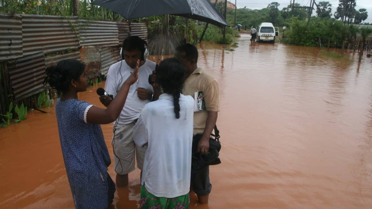 A group of people stand in deep water on a flooded street
