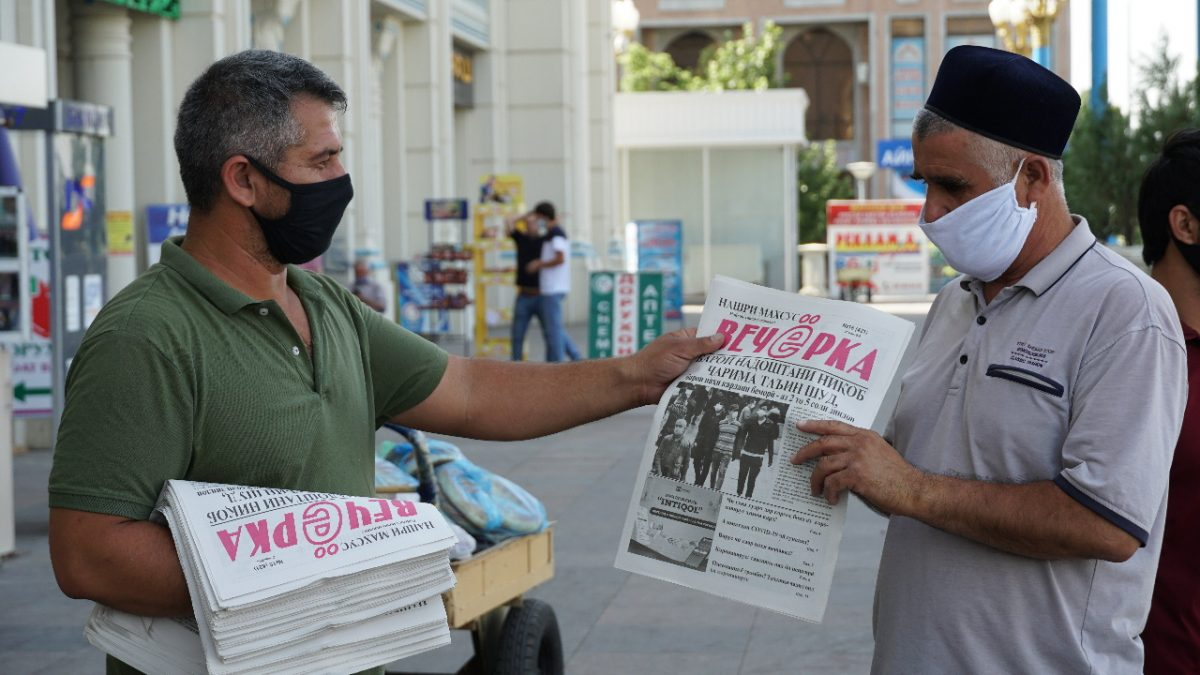 A man wearing a face covering hands a newspaper to another man
