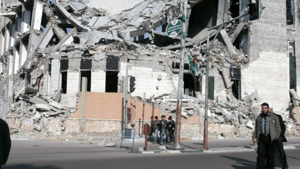 People walk in the street past a bombed building