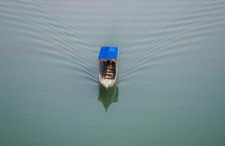 A small boat with a roof floats on the water.