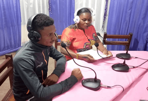A man and a woman sit at mics in front of a table in a radio studio