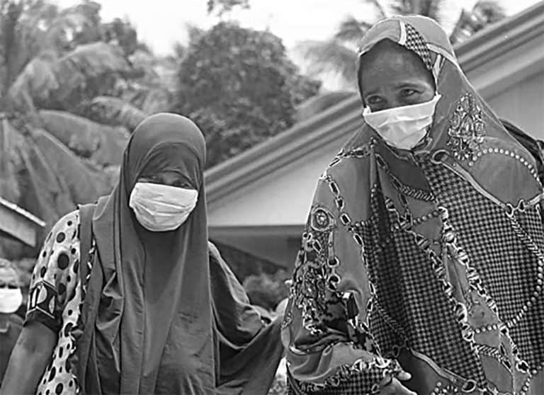 Two women wearing face masks stand outside a house.