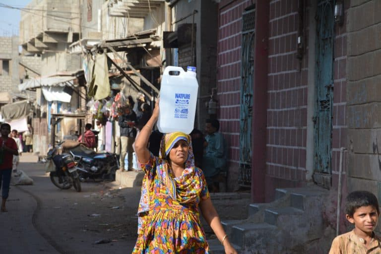 A woman walks down a street carrying a large plastic bottle on her head.