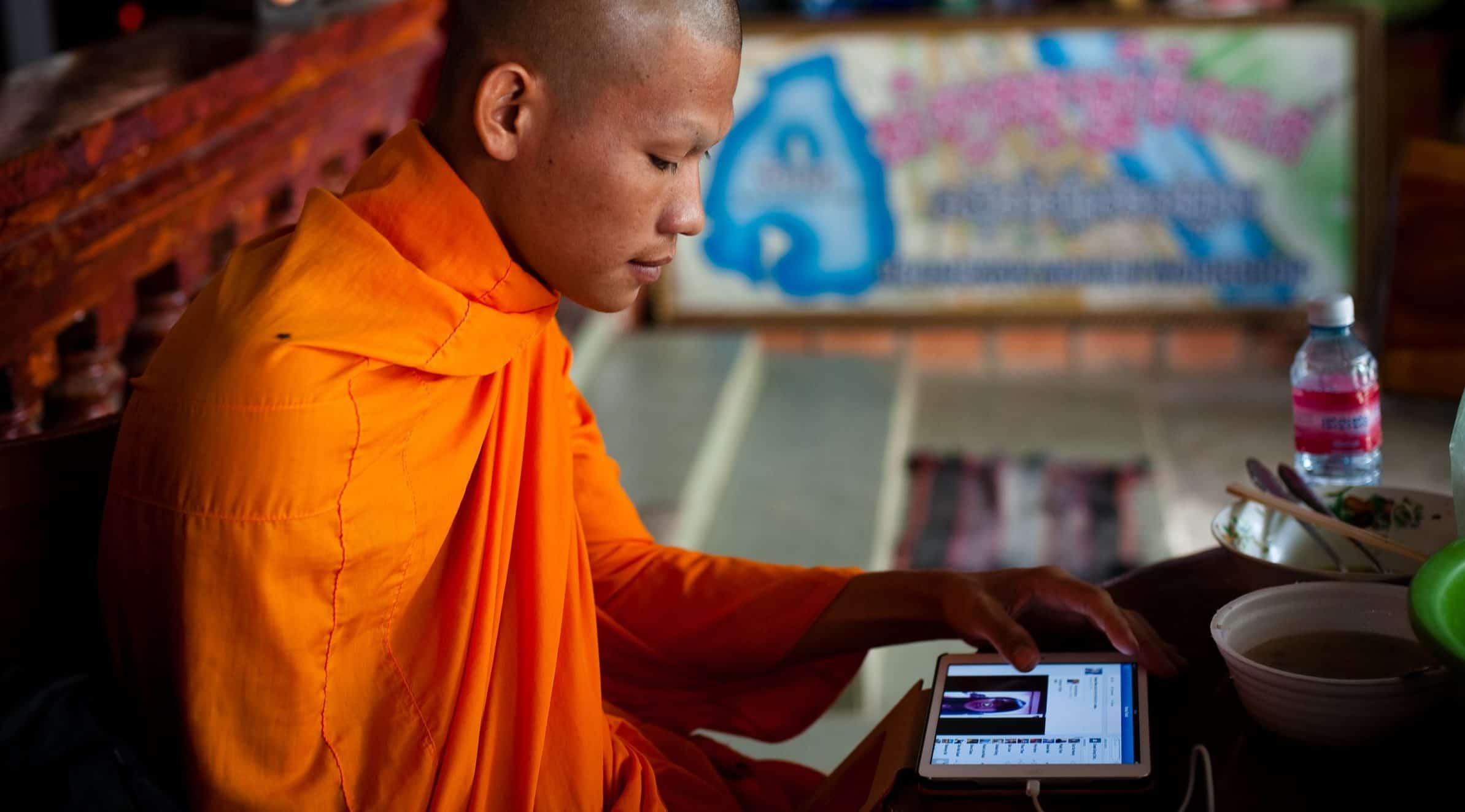 A man wearing an orange robe holds a tablet