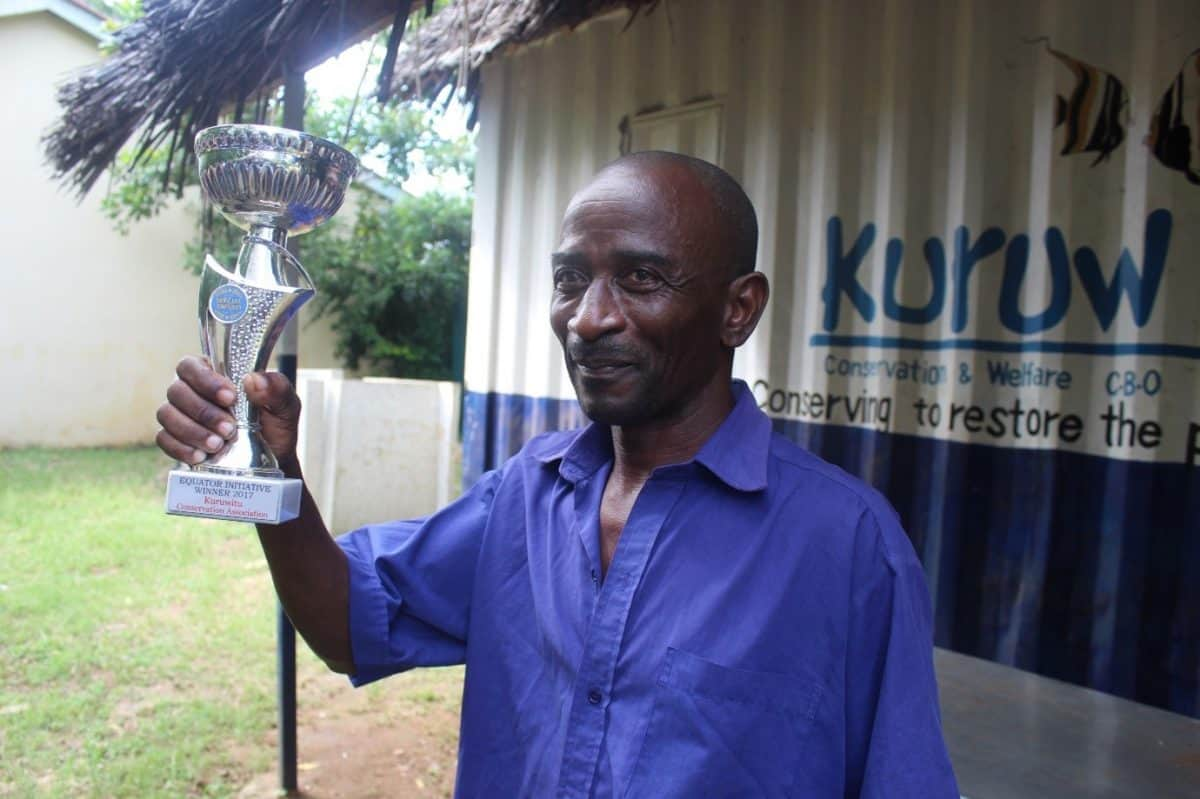 A man stands outside a metal building holding an award in his hand