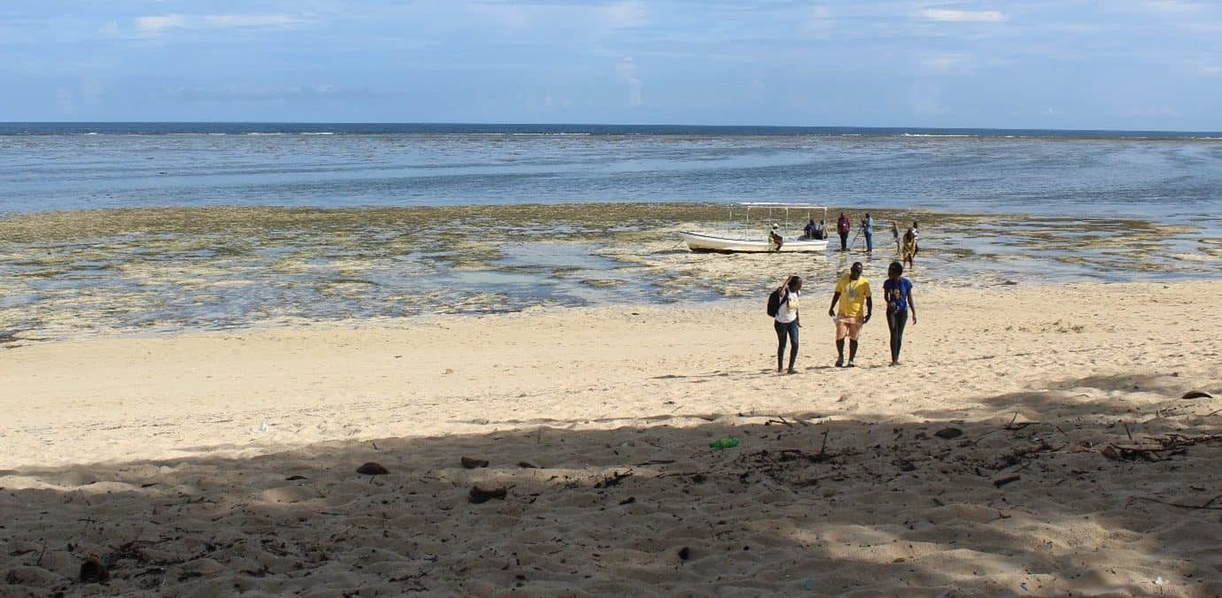 Three people walk on the beach; behind them in the surf are a group of people with a boat.