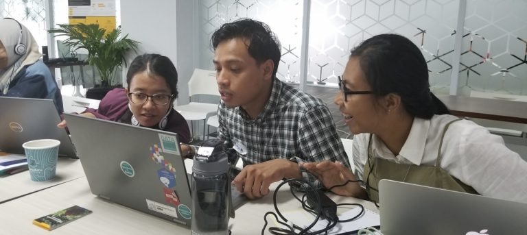 Two women and a man look at a laptop computer